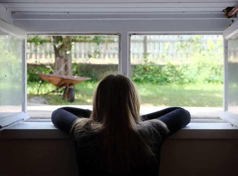 Young woman looking out of window